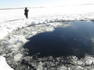 A policeman works near an ice hole at lake Chebarkul, said by the Interior Ministry department for Chelyabinsk to be the point of impact of a meteor